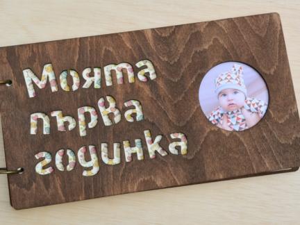 """Бебешки албум с дървени корици с надпис """"Моята първа годинка""""."""